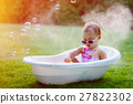 little baby girl bathes in bath on meadow 27822302