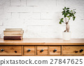 shelf with books and flower and white wall 27847625