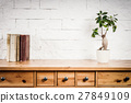 shelf with books and flower and white wall 27849109