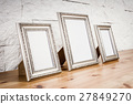 shelf with frames and white wall 27849270