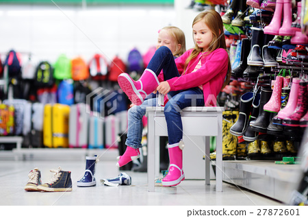 Two sisters choosing and trying on rain boots 27872601