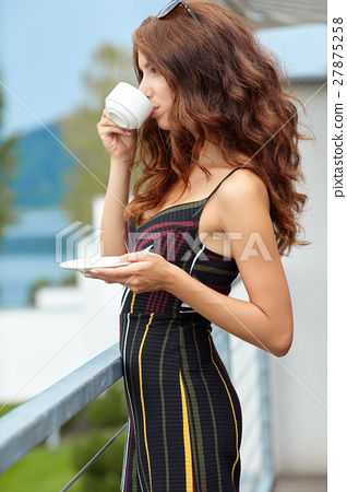 Beautiful woman relaxing on terrace house next lake background 27875258