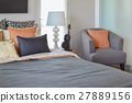 modern bedroom with orange pillow on grey chair 27889156