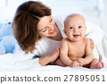 Baby and mother at home in bed. Mom and child. 27895051