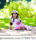 Little girl with roller skate shoes in a park 27895703