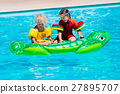 Kids in swimming pool with inflatable toy 27895707