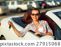 Woman sitting in a convertible car with the keys 27915068