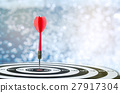 Red dart arrow on center of dartboard over bokeh b 27917304