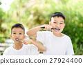 Boy brushing teeth in the garden 27924400