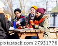 Young friends talking at picnic outdoors in park 27931776