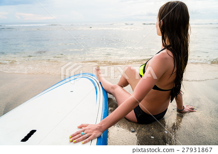 Female surfer sitting on Board after Surfing  27931867