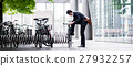 Businessman parking his bicycle in town 27932257