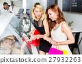 Couple of ladies choosing food in a restaurant 27932263