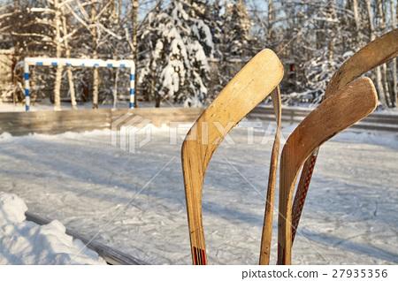 Hockey-sticks on ice rink 27935356