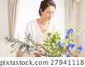 中年妇女在客厅里生活着美丽的花朵 27941118