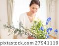 中年妇女在客厅里生活着美丽的花朵 27941119