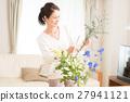 中年妇女在客厅里生活着美丽的花朵 27941121