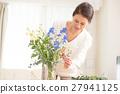 中年妇女在客厅里生活着美丽的花朵 27941125