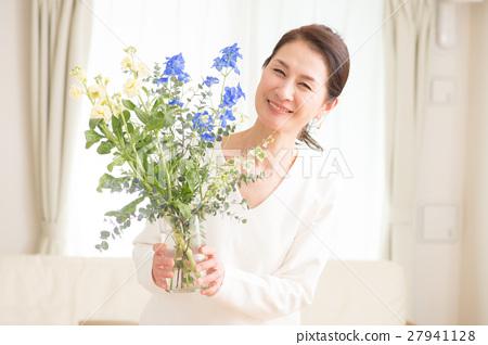 中年婦女在客廳裡生活著美麗的花朵 27941128