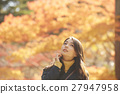 A woman enjoying autumn leaves 27947958