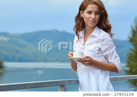 Beautiful woman relaxing on terrace house next lake background 27951159