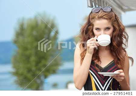 Beautiful woman relaxing on terrace house next lake background 27951401