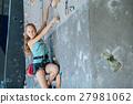 One teenager climbing a rock wall indoor. 27981062