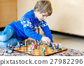 Little preschool kid boy playing chess game at 27982296