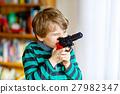 Cute little preschool kid boy playing with gun at 27982347
