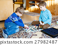 Two little kid boys playing chess game at home. 27982487