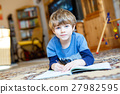 Happy school kid boy at home making homework 27982595