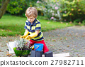 Funny little kid boy planting flowers in garden on 27982711