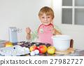 Funny blond kid boy baking apple cake indoors 27982727