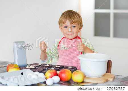 Funny blond kid boy baking apple cake indoors 27982727