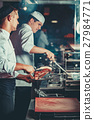 Busy chefs at work in the restaurant kitchen 27984771