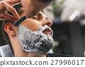Barber shaving stubble of client 27996017