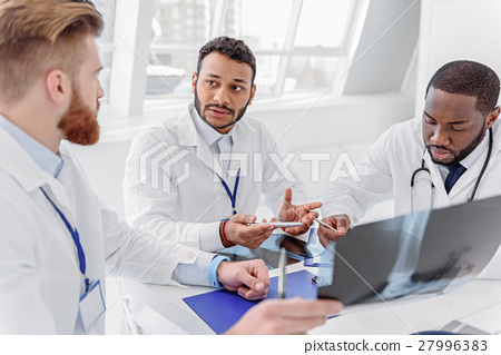 Serious doctors analyzing radiograph on council 27996383
