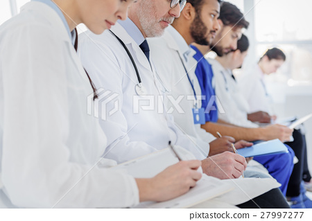 Pensive medical team making notes at clinic 27997277