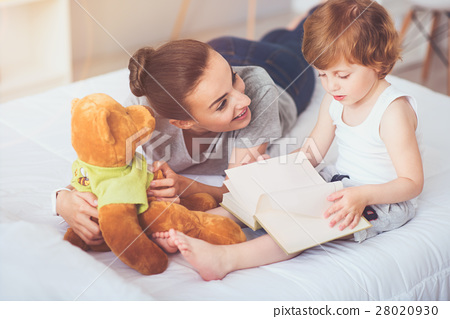 Joyful mother teaching her son to read. 28020930