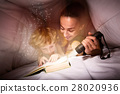Pretty woman and her son reading a book at night 28020936
