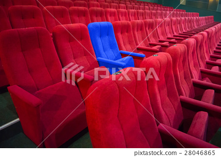 Blue chair between rows of red seats 28046865