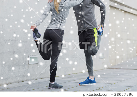 close up of couple stretching legs outdoors 28057596