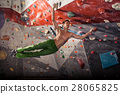 man practicing rock-climbing on a rock wall indoors 28065825