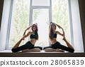 Two young women doing yoga asana Eka Pada Rajakapotasana on wind 28065839