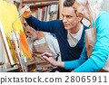 Delighted artist showing elderly woman how to 28065911
