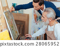 Concentrated artist helping elderly man in 28065952