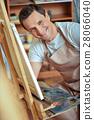 Happy artist posing in painting studio. 28066040