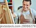 Satisfied artist posing in painting studio 28066278