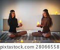 Two young women meditating in lotus pose holding candles on plai 28066558