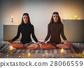 Two young women meditating in lotus pose on plaid in cozy room w 28066559